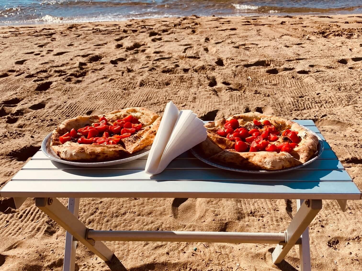 Pizza wird am Strand serviert